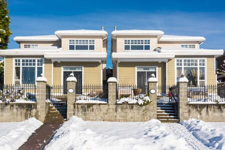 Residential duplex house with front yard in snow on winter sunny day in Canada