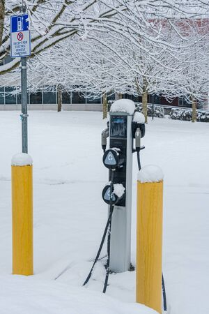 Electric car charging station on winter season covered with snow. Electric charging point on white snow background