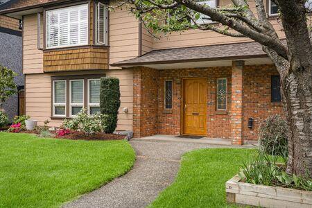 Schöner Haupteingang des alten Einfamilienhauses mit strukturierter Ziegelwand und Betonweg über Vorgartenrasen Standard-Bild