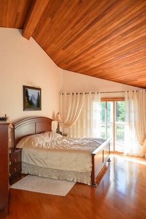 Beautiful bedroom with wooden ceiling and sun light coming through glass door.