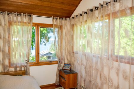 Wide windows and curtains in small bedroom with ocean bay view. 免版税图像