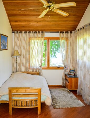Small lightful bedroom with curtains on windows and rug on the floor. 免版税图像