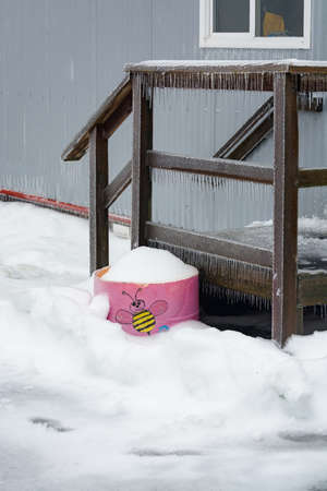 Ice covered doorsteps of portable building with pink flowerbed on side