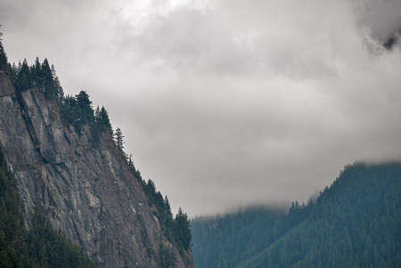 Steep rocky mountain cliff surrounded by trees on overcast sky background 免版税图像