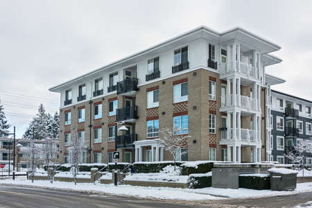 Residential low-rise building on winter day with white sky background