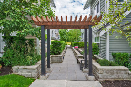 Walkway in residential area between two rows of townhouses with unit for sale