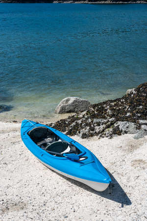 Blue lightweight canoe boat on a shore of ocean bay on sunny day