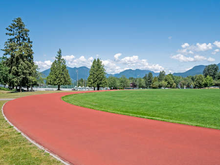 Red jogging track of recreational stadium on bright sunny day