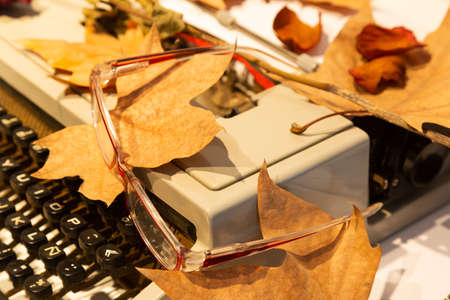 eyeglasses on a typewriter with autumn leaves in the house