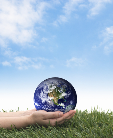 Hands holding earth over grass on a blue sky. Environmentally friendly. Stock Photo