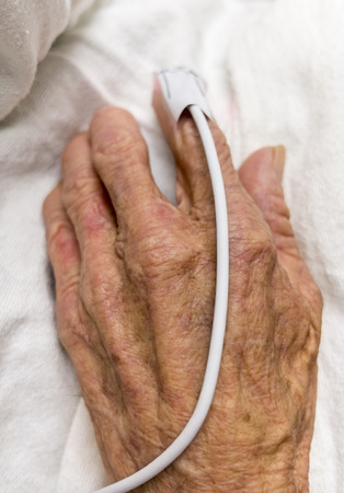 dedo indice: Elderly hand with a pulse meter on index finger