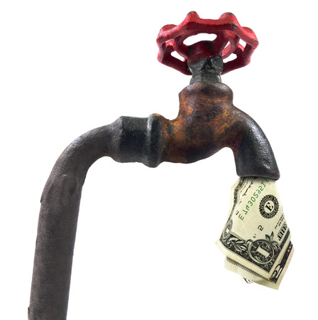 Isolated faucet with cash on a white background. Stock Photo