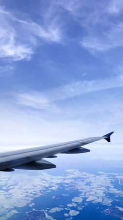 sea scape: Aircraft wing over the earths atmosphere Stock Photo