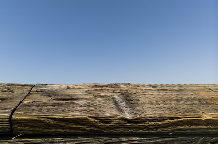 Weathered wood rail on a blue sky. Stock Photo