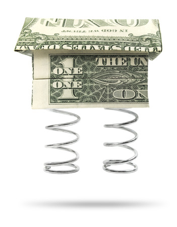 Real estate boom. Isolated origami cash home with a metal coil spring.