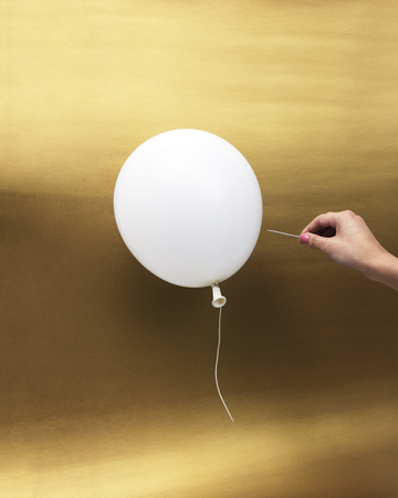 Hand with pin popping a white balloon