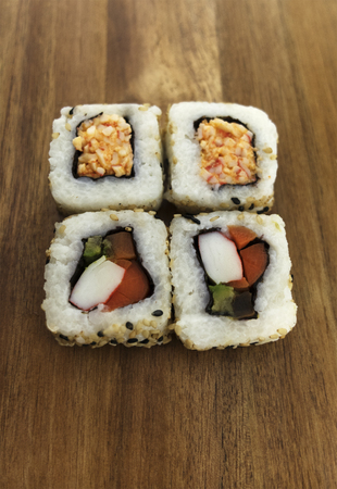 Top View of sushi rolls on a wood background.