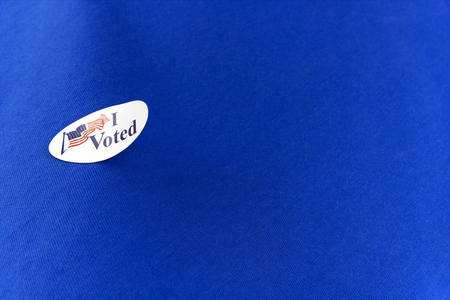 Peeling, curled election voting sticker on a blue cotton clothing shirt.