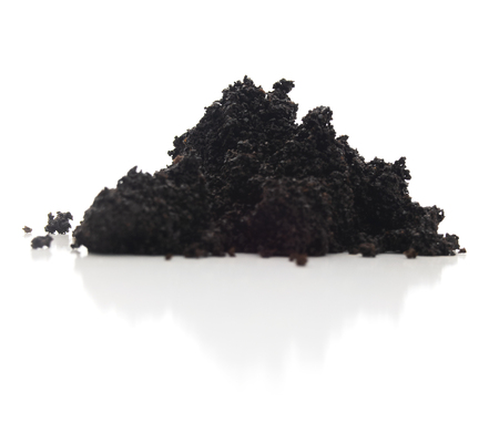 Low view of isolated stack brewed coffee bean grounds on a white background.