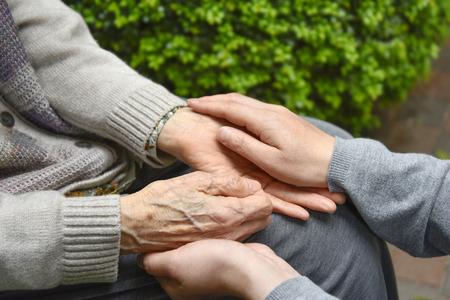 高齢者介護の老婆コンセプトの手に触れる