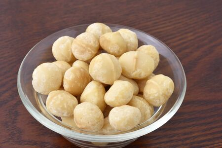 Macadamia nuts on wooden table 写真素材 - 132725359