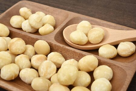 Macadamia nuts in wooden dish 写真素材 - 132725416