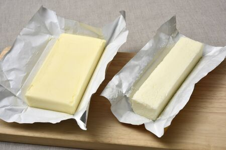 Yellow and white butter on wooden cutting board 写真素材