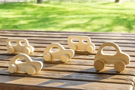Wooden Toy Cars on Table Wooden on Green Grass Background. Stok Fotoğraf