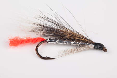 Fly fishing lure isolated against a neutral background photo