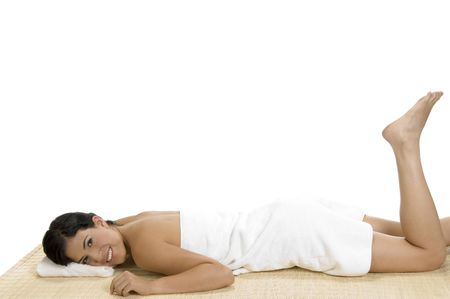 rejuvenating: pleased woman laying on bamboo mat