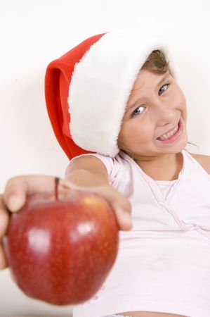 smiling little girl with christmas hat showing apple photo