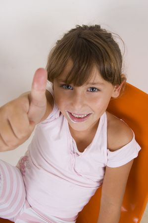 8 year old: smiling cute little girl showing thumbs up hand gesture
