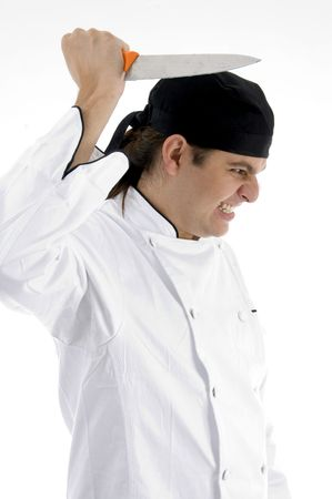 angered chef posing with knife against white background photo