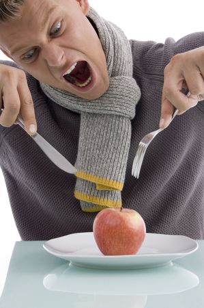 young man going to eat apple with fork and knife on an isolated background photo