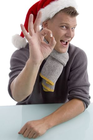 smiling young man with christmas hat showing ok gesture on an isolated background photo