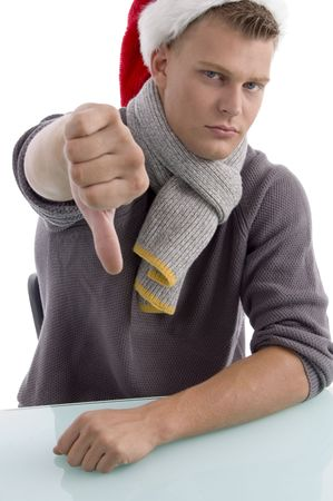young man with christmas hat showing thumb down with white background photo
