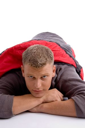 sleeping bag: young man covered himself with red sleeping bag against white background