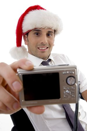 photographer man with christmas hat showing his digital camera with white background photo