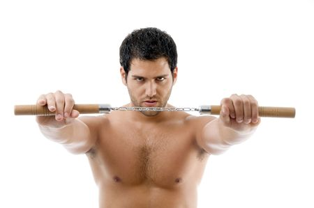 portrait of young man with nunchaku on an isolated background photo