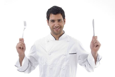 chef holding crossed fork and knife against white background photo
