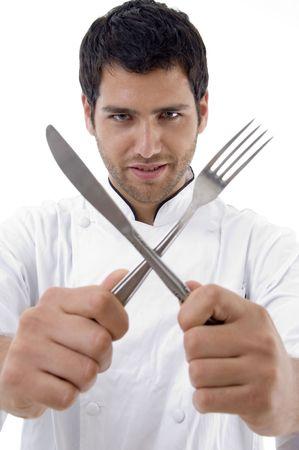 chef holding crossed fork and knife against white background Standard-Bild