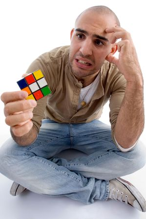 confused male holding puzzle cube with white background