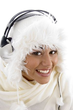 21: pretty girl wearing winter clothes and listening to music with white background