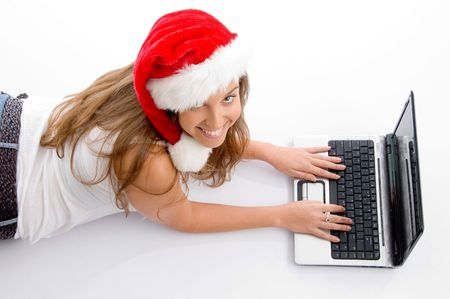 laying female with christmas hat and laptop against white background photo