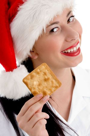woman with christmas hat and holding biscuit on an isolated white background photo