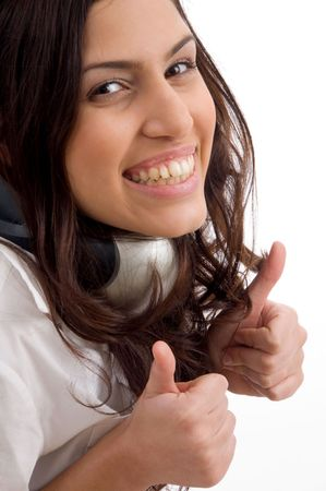 21: caucasian female wearing headphones and gesturing thumbs up against white background