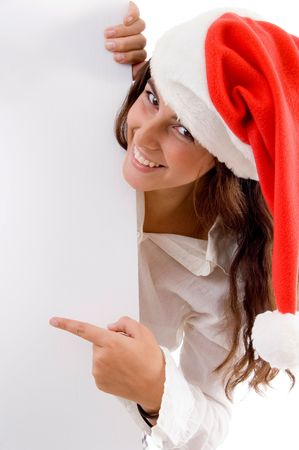 female wearing christmas hat and pointing placard on an isolated white background photo