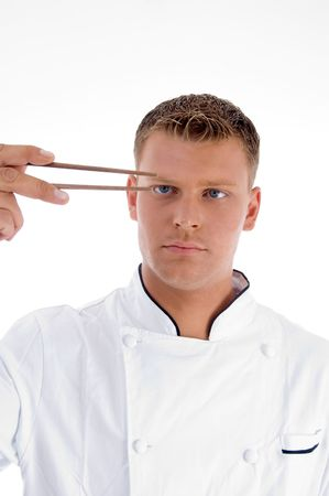 chef looking chopsticks against white background photo