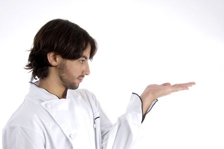 young chef looking his palm on an isolated background photo