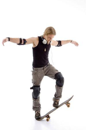 actief luisteren: avonturieren man balancing skateboard tegen een witte achtergrond  Stockfoto